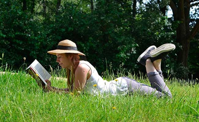 woman in grass reading a book